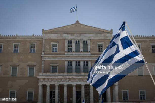 Greek flag seen front of the Greek Parliament at the demonstration. People demonstrated in Syntagma square, Athens, in protest at the Greek...