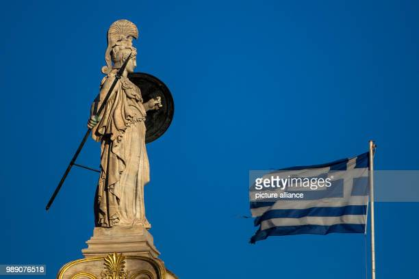 A Greek flag waves by the statue of the goddess Athena in Athens on June 29 2018 Photo Angelos Tzortzinis/dpa