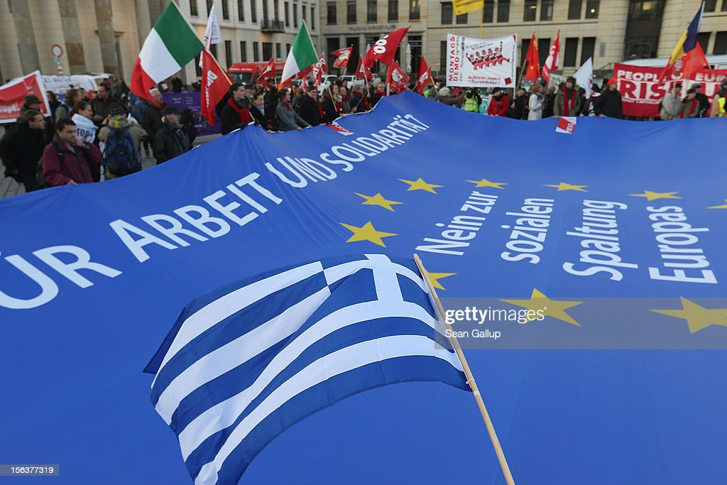 "A Greek flag waves over a giant flag of the European Union with slogans that read: 'For Work And Solidairty, No To The Division Of Europe' during a ""national day of action"" by protesters demonstrating in solidarity with the economically-stricken nations of southern Europe in front of the Brandenburg Gate and organized by the German Federation of Labour Unions (DGB) on November 14, 2012 in Berlin, Germany. The DGB called for nationwide protests to coincide with strikes taking place today in Spain, Portugal, Greece, Italy and Belgium over government austerity measures meant to combat the ongoing Eurozone financial crisis."