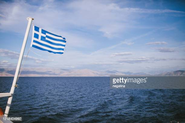greek flag waving above the sea in front of the mountain landscape - ferry stock pictures, royalty-free photos & images