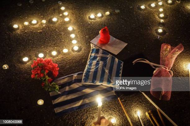 Greek flags seen during the vigil service People gathered outside the Hellenic Parliament in memory of the 91 victims of the deadly fire in Eastern...