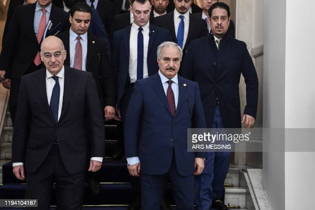 Greek Foreign Minister Nikos Dendias and Libyan strongman Khalifa Haftar leave after talks in Athens, on January 17 days ahead of a peace conference...