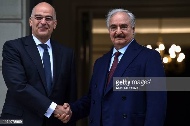 Greek Foreign Minister Nikos Dendias welcomes Libyan strongman Khalifa Haftar before talks in Athens, on January 17 days ahead of a peace conference...