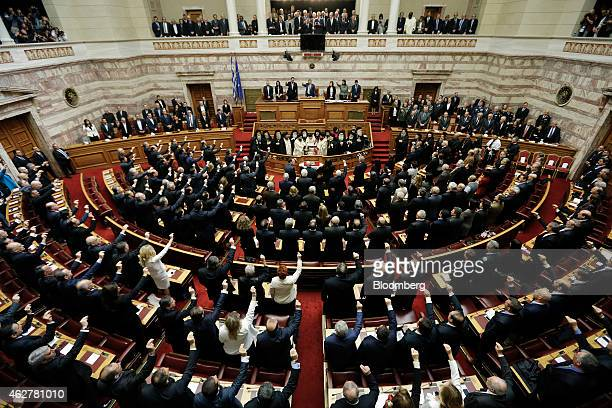 Greek lawmakers are seen raising their hands during the official swearingin ceremony for the new government lead by Alexis Tsipras Greece's prime...