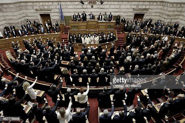 Greek lawmakers hold up their right hands as they take part in a swearingin ceremony for the new deputies that were elected in the January 25...