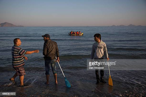 Greek man confronts two migrant men to argue over the fate of a dingy and its battery and motor as migrants paddle towards the shore after completing...