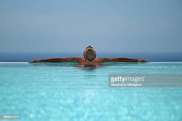 Greek man relaxing inside a pool in Santorini island, Greece.