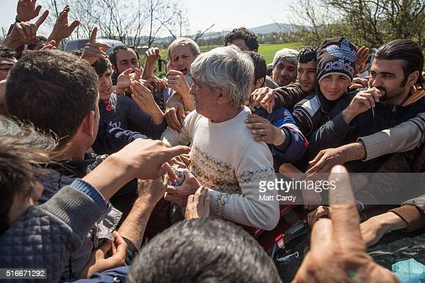 Greek man tries to distribute aid from the back of his car at the Idomeni refugee camp on the Greek Macedonia border on March 20 2016 in Idomeni...