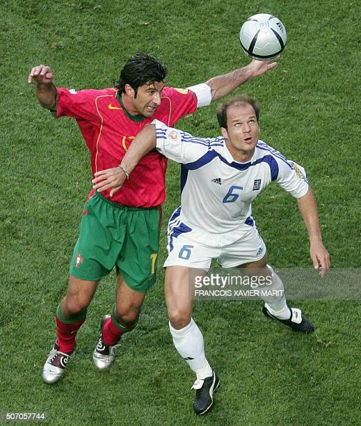 Greek midfielder Angelis Basinas vies with Portuguese forward Luis Figo 04 July 2004 at Stadio da Luz in Lisbon during the Euro 2004 final football...