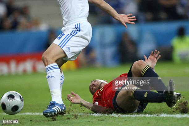 Greek midfielder Nikos Spiropoulos controls the ball as Spanish forward Sergio Garcia lays on the ground during the Euro 2008 Championships Group D...