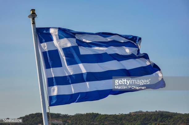 greek national flag blowing in wind, greece - greek flag stock pictures, royalty-free photos & images