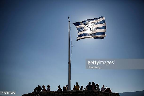 A Greek national flag flies above tourists on Acropolis Hill in Athens Greece on Wednesday July 8 2015 The European Union set a Sunday deadline to...
