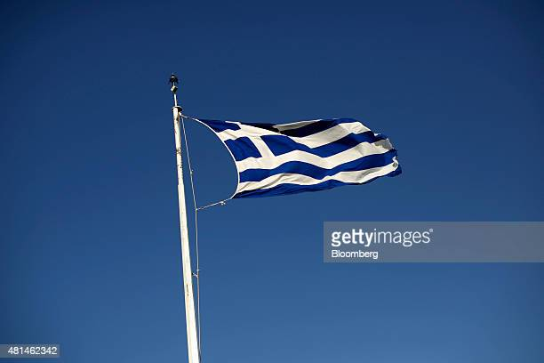 A Greek national flag flies from a flagpole on Acropolis Hill in Athens Greece on Monday July 20 2015 German Chancellor Angela Merkel held out the...