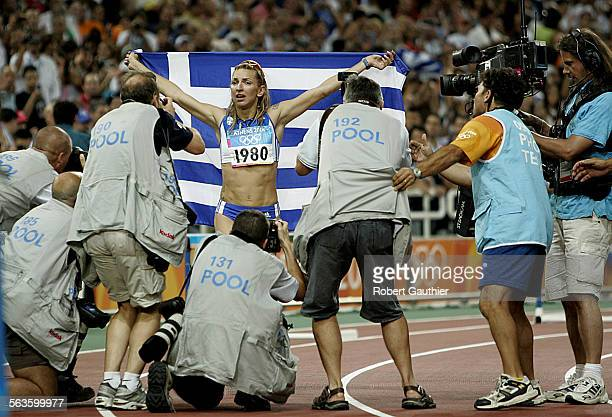 Greek Olympian Fani Halkia is mobbed by photographers as she takes a victory lap after winning the 400 meter hurdles gold medal at the Olympic...