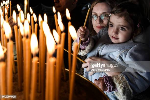 Greek Orthodox believers light candles during Good Friday's 'Apokathelosis' the lowering of Christ's dead body from the Cross which forms a key part...