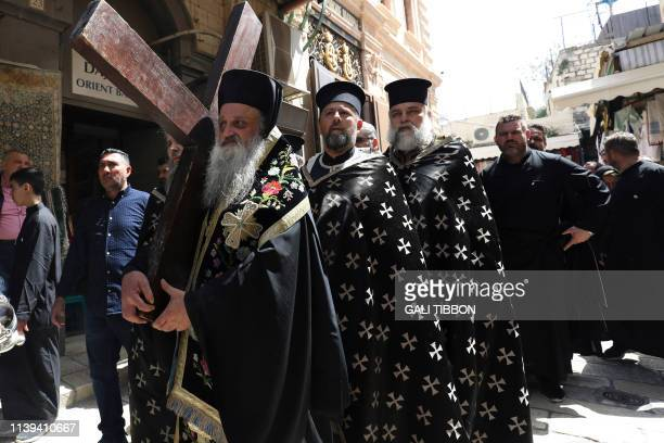 A Greek Orthodox bishop carries a large wooden cross as they celebrate the Good Friday in procession on Via Dolorosa in the Old City of Jerusalem on...