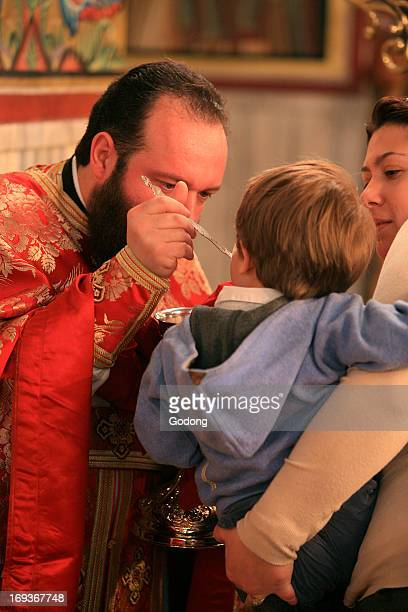 Greek orthodox boy receiving the eucharist
