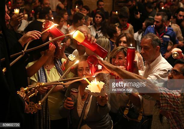 Greek Orthodox Christians light candles from their Patriarch and share the Holy Fire which was brought from Jerusalem through Amman at the Saint...