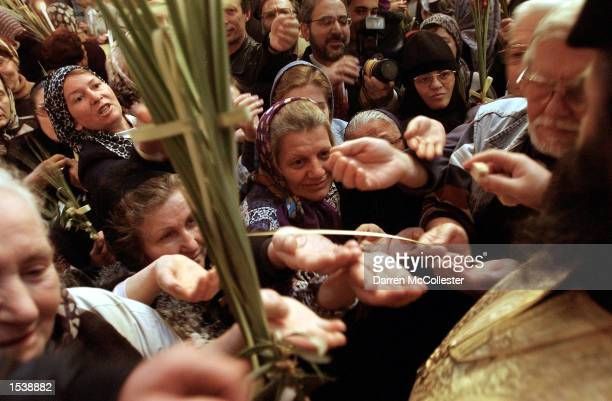 Greek Orthodox Christians reach for the bread of Christ April 28 2002 at the Church of the Holy Sepulchre in the Old City of Jerusalem Israel The...