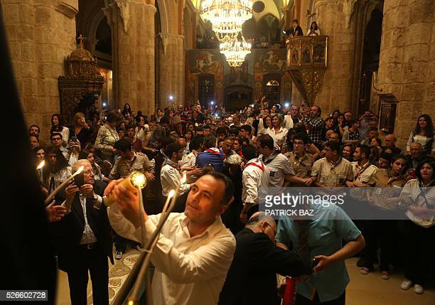 Greek Orthodox Christians share the Holy Fire that was brought from Jerusalem through Amman at the Saint George church in downtown Beirut on April 30...