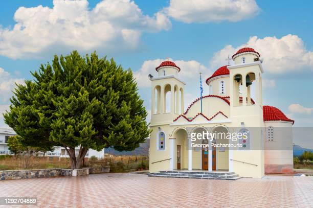 greek orthodox church next to a large tree - greek orthodoxy stock pictures, royalty-free photos & images