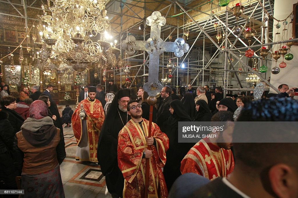 greek orthodox clergies walk during the midnight mass at the church of the nativity in the