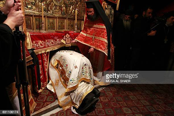 Greek Orthodox Clergy pray in the Grotto during the midnight mass Patriarch of Jerusalem Theophilos III Leads the midnight mass at the Church of the...