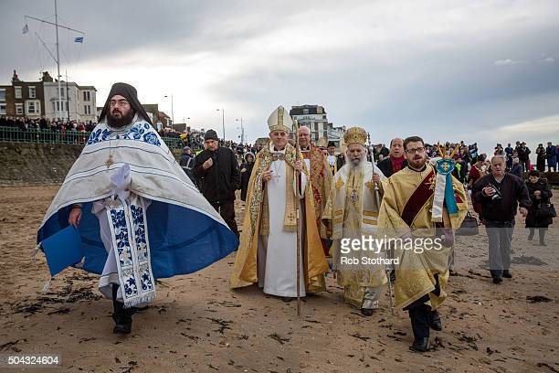 Greek Orthodox clergy walk on Margate beach after offering a blessing for the Feast of the Epiphany on January 10 2016 in Margate England Greek...