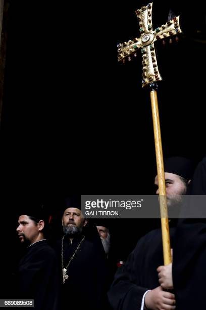 A Greek Orthodox clergyman carries a cross during the Easter Sunday procession in Jerusalems Old City on April 16 2017 Thousands of Christians marked...