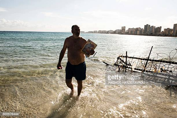 A Greek Orthodox Cypriot holding an icon comes back from the fencedoff touristic area of Varosha in the eastern port city of Famagusta in the...