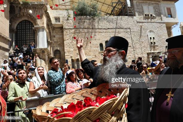 A Greek Orthodox monk tosses rose petals during the Easter Sunday procession in front of the Church of the Holy Sepulchre in Jerusalem's Old City on...
