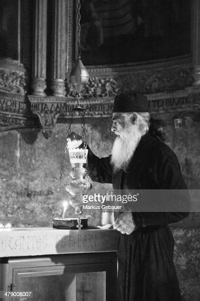 Greek Orthodox on his morning procedure of light the oil lamps inside the Church of the Holy Sepulcher.