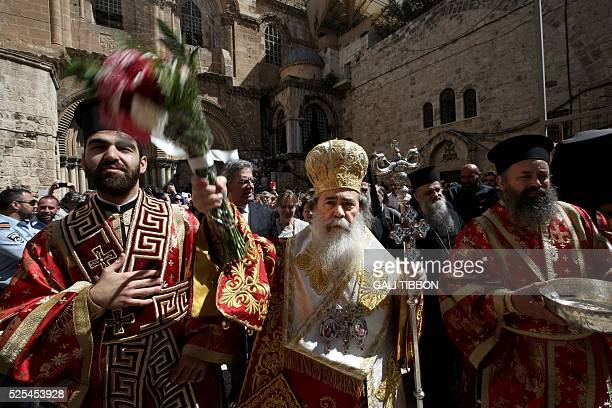 Greek Orthodox Patriarch of Jerusalem Theophilos III sprinkles holy water at worshippers after the Washing of the Feet ceremony in front of the...