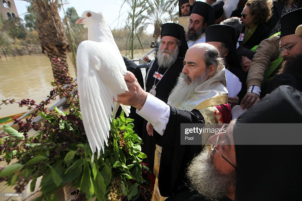 Greek Orthodox Patriarch Theophilos III of Jerusalem holds a white dove and prays during a traditional Epiphany ceremony at the baptismal site of Qasr el-Yahud near the West Bank city of Jericho on January 18, 2013. Thousands of Orthodox pilgrims come every year to the celebrate where it is believed that Jesus was baptised.