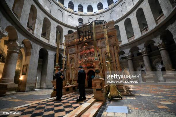Greek Orthodox priest and a caretaker stand in front the deserted Edicule in the Church of the Holy Sepulchre, traditionally believed to be the...