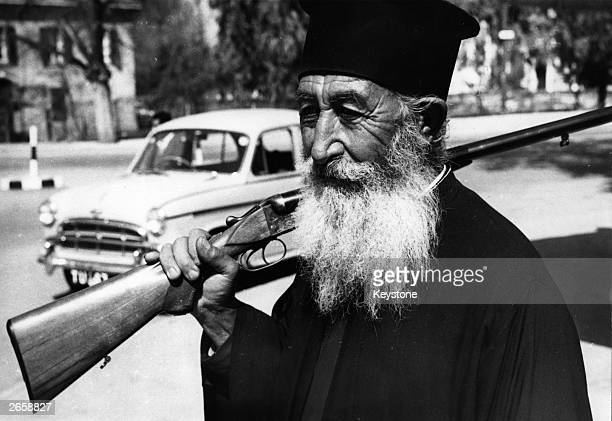 Greek Orthodox priest at Nicosia with a rifle on his shoulder during outbreaks of violence in Cyprus following independence. He is a member of the...