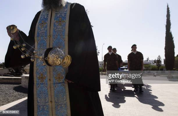 A Greek orthodox priest burns incense as members of Cyprus armed forces carry coffins during a burial ceremony to hand over the unidentified remains...