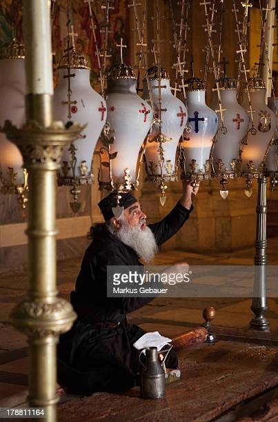 Greek Orthodox priest changing oil in lamps at the Church of the Holy Sepulchre in Jerusalem, Israel