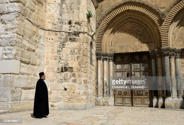 Greek Orthodox priest gazes at the closed door of the Church of the Holy Sepulchre in the Old City of Jerusalem following the closure of the city for...