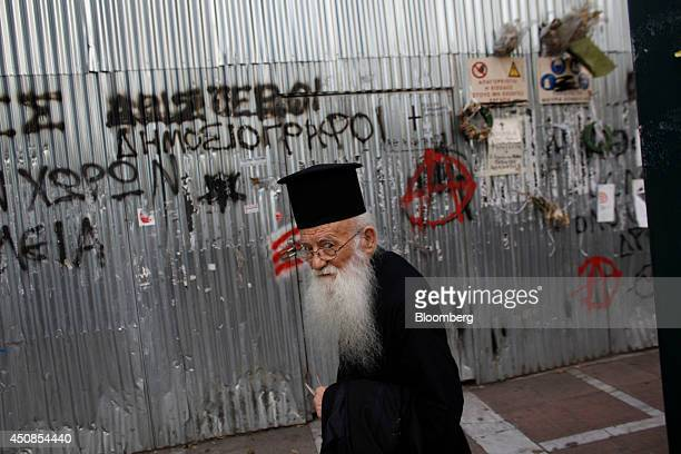 A Greek orthodox priest passes wreaths and tributes on a temporary shrine to Marfin Egnatia bank workers killed during violence at the start of the...