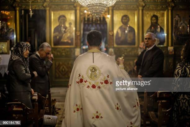 A Greek Orthodox priest prays during the Orthodox Christmas mass at the Saint Porphyrius church in Gaza Gaza City 07 January 2018 Photo Mohammed...