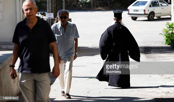 A Greek orthodox priest right passes voters arriving at a polling station to cast their votes in the second round of the Greek general elections in...