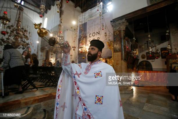 Greek Orthodox priest swings the incense thurible at the altar, at the beginning of the first Sunday mass at the Church of the Nativity after its...