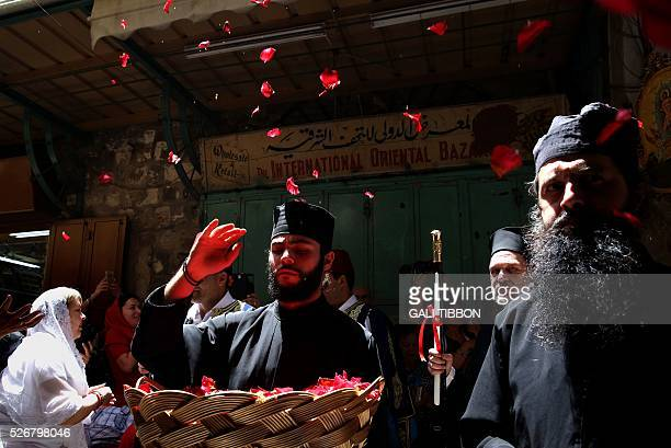 Greek Orthodox priest throws rose leaves during the Orthodox Easter Sunday procession to the Church of the Holy Sepulchre in Jerusalem's Old City on...