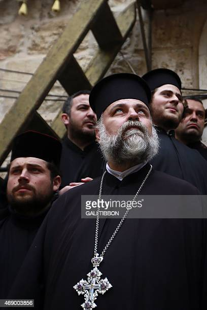 Greek Orthodox priests attend the traditional Washing of the Feet ceremony during the Holy Thursday Easter procession at the Church of the Holy...