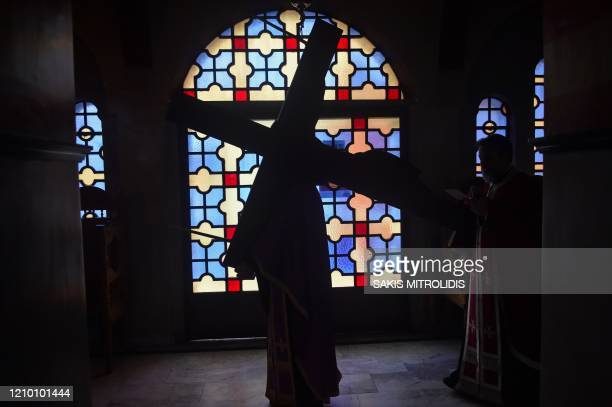 TOPSHOT Greek Orthodox priests carries an image of Jesus Christ on the cross in an empty church due to the spread of the novel cornoavirus during a...