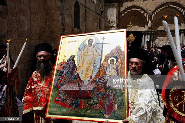 Greek Orthodox priests carry an icon depicting Jesus Christ's resurrection during the Orthodox Easter Sunday procession in front of the Church of the...