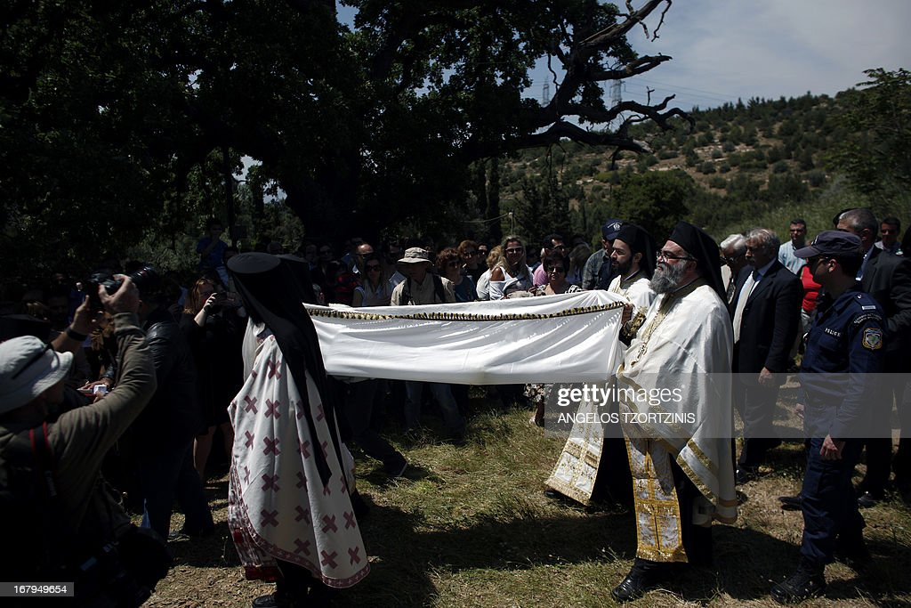 Greek Orthodox priests carry out the Apokathelosis, carrying the 'body' of Jesus Christ to a tomb, which forms a key part of Orthodox Easter, in a ceremony at the Church of the Dormition of the Virgin in Penteliin Penteli, north Athens on May 3 , 2013. Millions of Greeks flock to churches around the country this week to celebrate Easter, the country's foremost religious celebration. AFP PHOTO / Angelos Tzortzinis