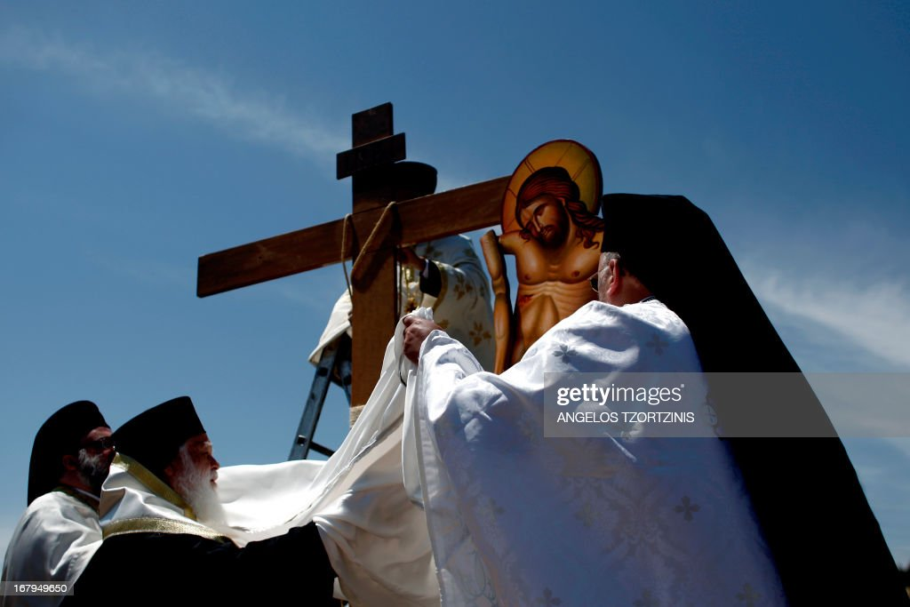 Greek Orthodox priests carry out the Apokathelosis, the removal of Christ's dead body from the Cross, which forms a key part of Orthodox Easter, in a ceremony at the Church of the Dormition of the Virgin in Penteliin Penteli, north Athens on May 3 , 2013. Millions of Greeks flock to churches around the country this week to celebrate Easter, the country's foremost religious celebration. AFP PHOTO / Angelos Tzortzinis