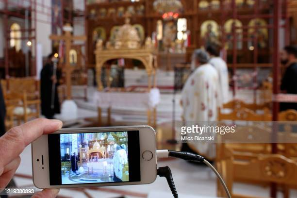 Greek Orthodox priests perform Holy Friday ceremony mass in empty church transmitted live on the web on April 17 2020 in Athens Greece As part of its...